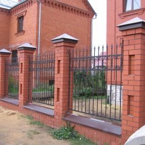 Металлический забор на кирпичных столбах