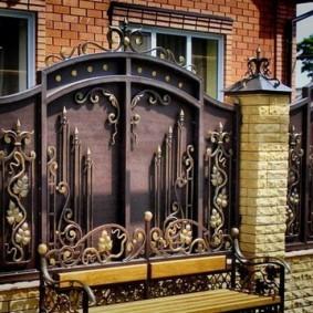 Кованая лавочка перед забором частного дома