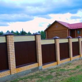 Забор с кирпичными столбами на склоне участка