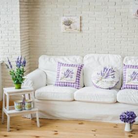 Светлый диван возле кирпичной стены