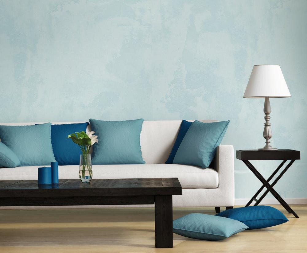 Нежно-голубые обои на стене за диваном