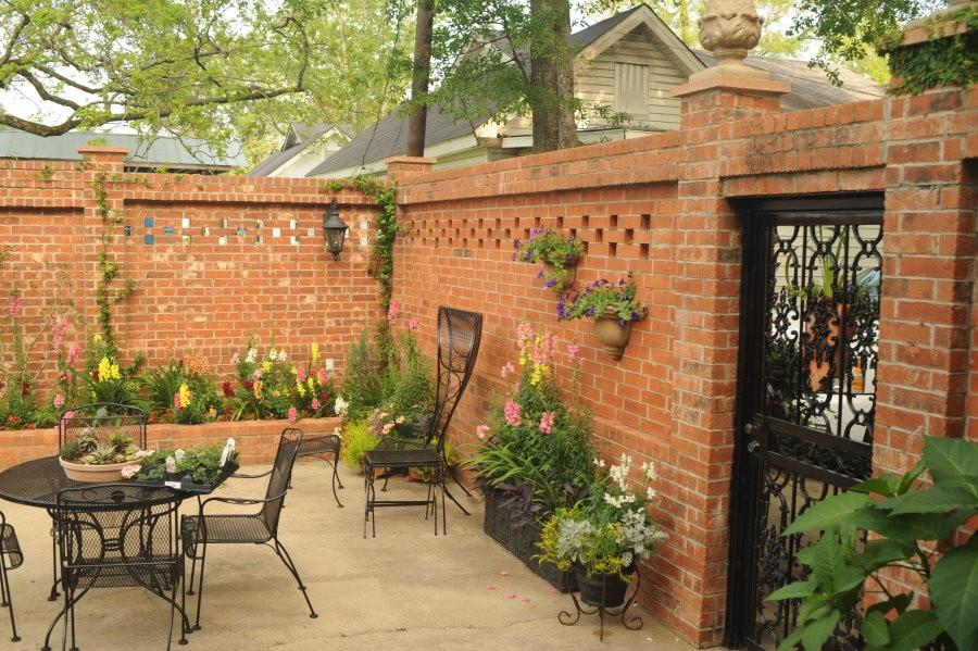 Внутренний дворик участка с кирпичным забором