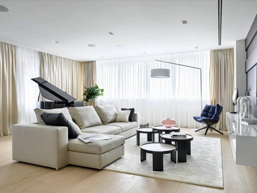 Массивный диван в зале с нейтральными шторами