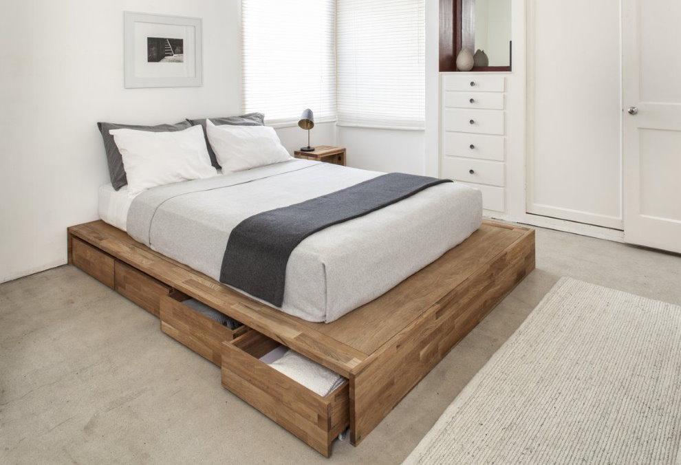Узкие ящики в деревянном подиуме под кроватью