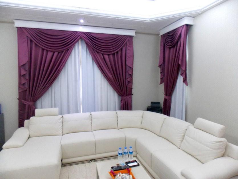 Шторы бордового цвета в зале с белым диваном