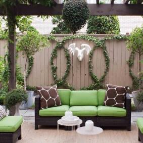 Садовый диванчик с зелеными подушками