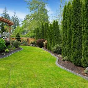 Узкий газон между домом и забором