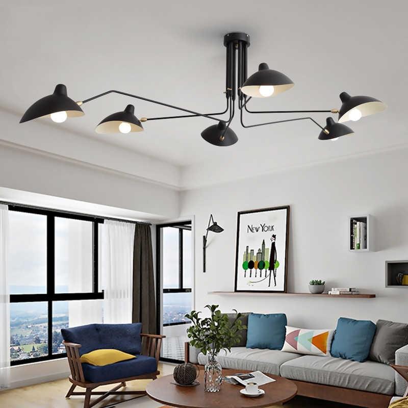 Черная люстра-паук на белом потолке зала