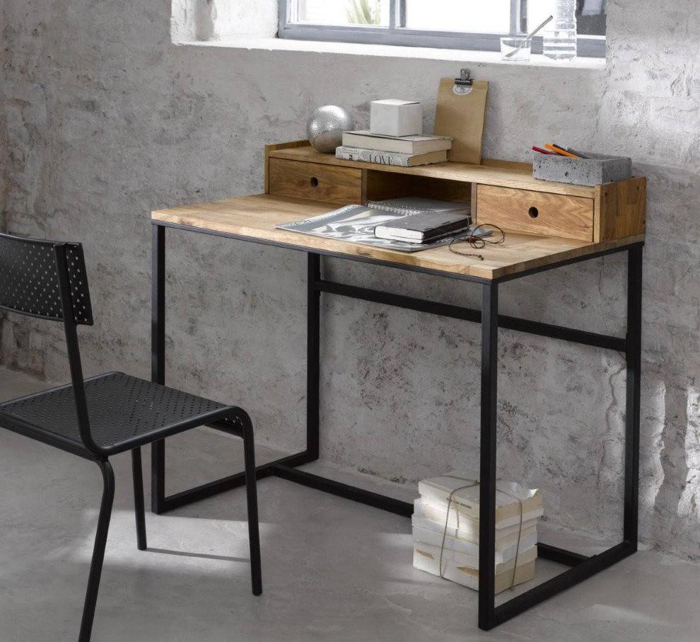 Металлический письменный стол на фоне бетонной стены