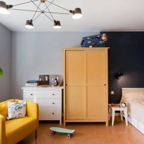 Желтое кресло под потолочной люстрой