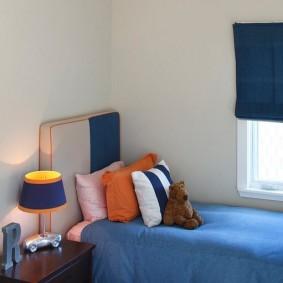 Оранжевый светильник над синей кроватью