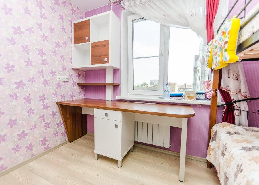 Письменный стол под подоконником в комнате девочки