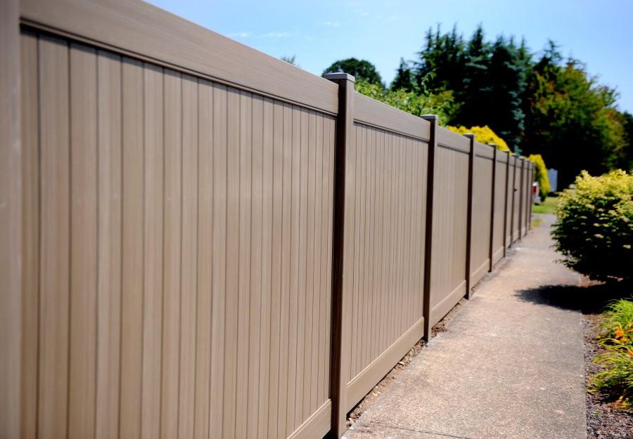 Коричневый пластиковый забор вдоль территории садового участка
