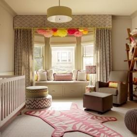 Полосатый коврик на полу комнаты для новорожденного