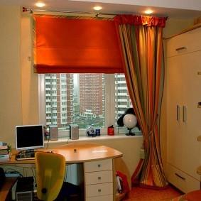 Письменный стол школьника перед окном в квартире