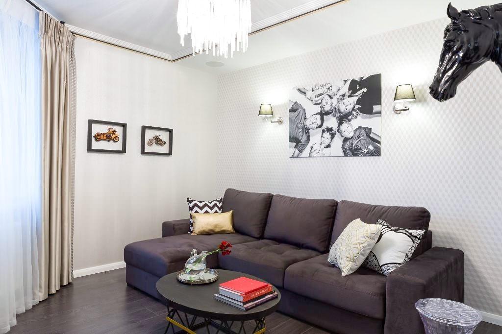 Темный диван в зале с белыми обоями