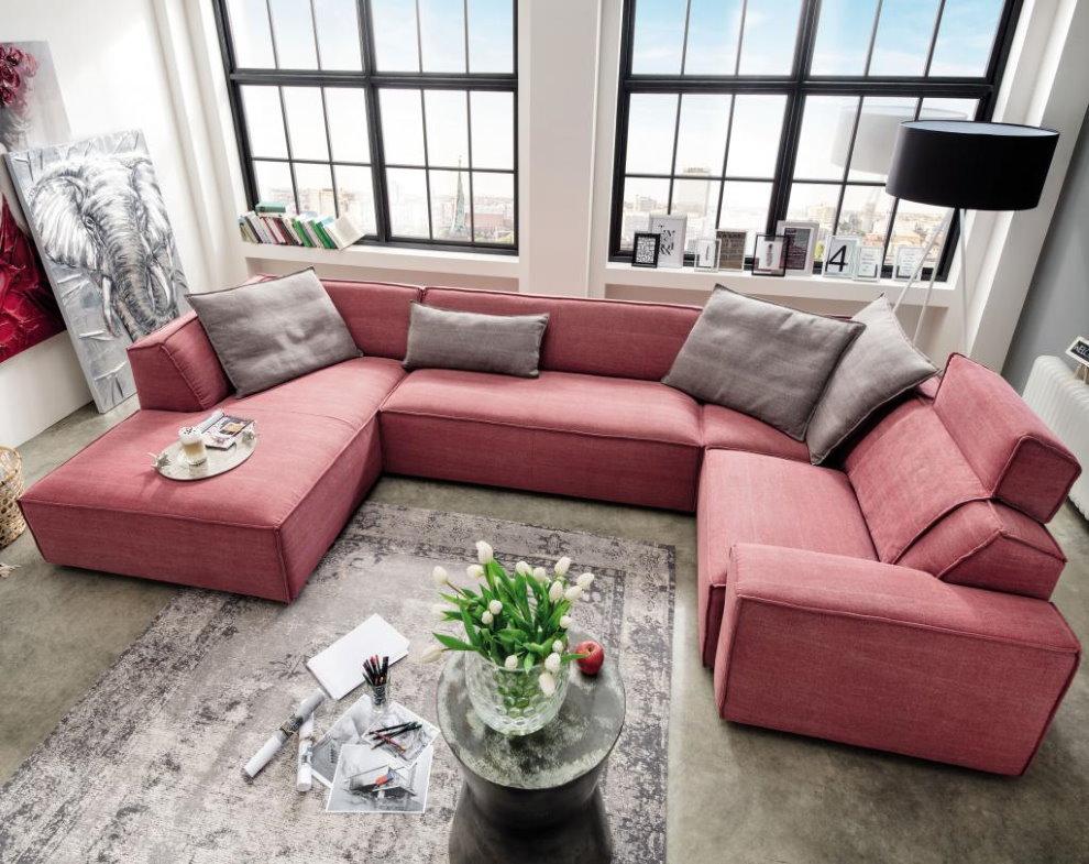 С-образный диван в зале с двумя окнами