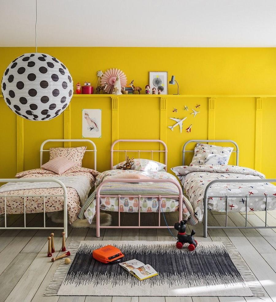 Детские кровати около желтой стены