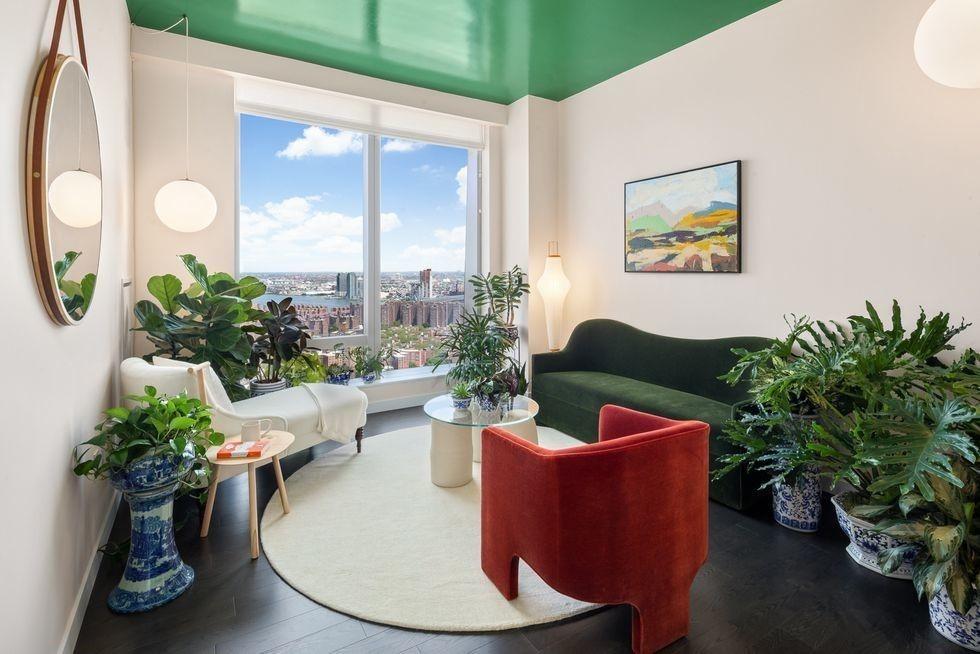 Зеленые растения в интерьере гостиной с большим окном