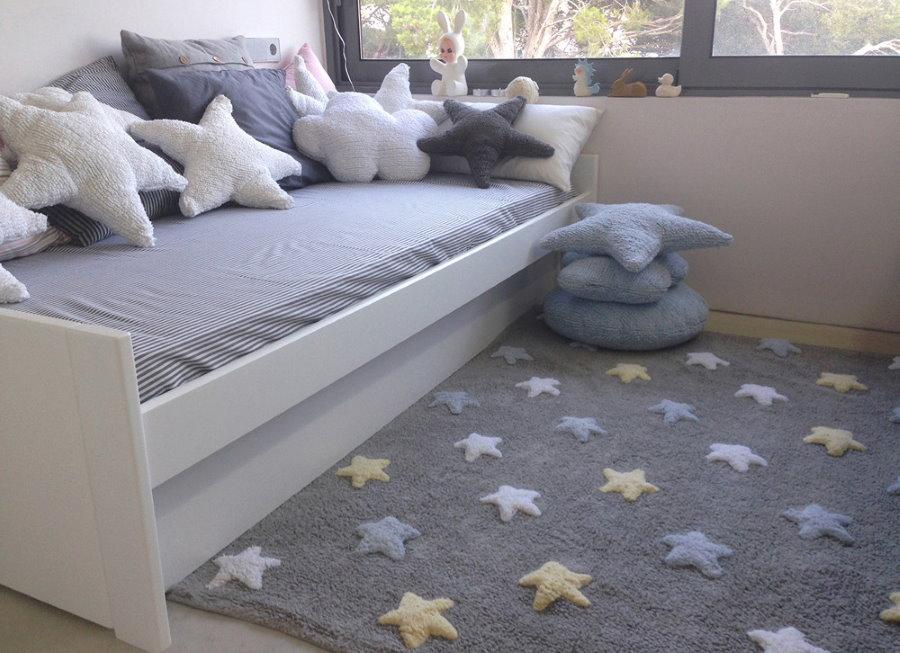 Серый коврик со звездами перед детской кроватью