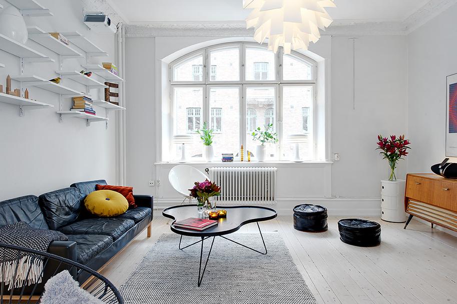 Черный диван в квартире с белыми стенами