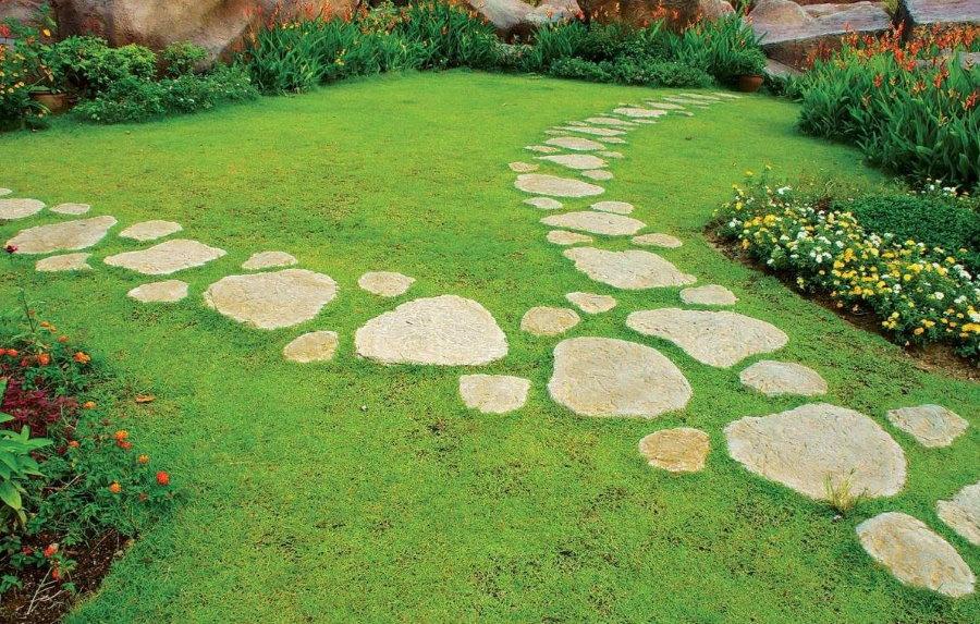 Дорожка из природного камня на зеленой лужайке