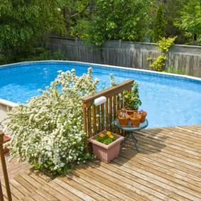 Каркасный бассейн на участке с деревянным забором