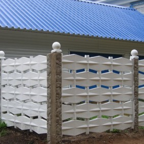 Белые шары на столбах бетонного забора