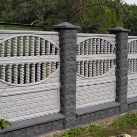 Белые секции бетонного забора на серых столбах