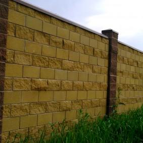 Блоки с разной текстурой в дачном заборе