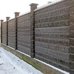 Бетонный забор зимой на дачном участке