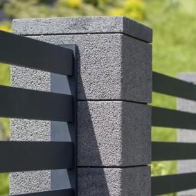 Крепление металлических секций забора к столбам из блоков