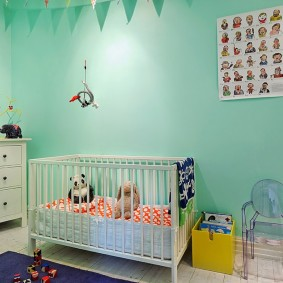 Кроватка для младенца около бирюзовой стены