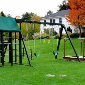 Зеленая трава под детскими качелями