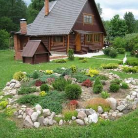 Небольшой альпинарий на участке с деревянным домом
