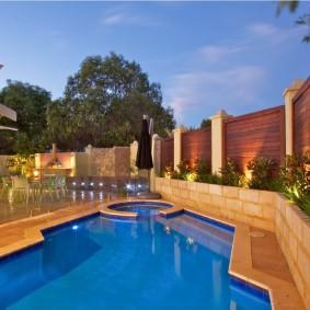 Открытый бассейн на участке с деревянным забором