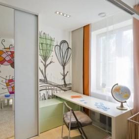 Письменный стол перед окном детской комнаты