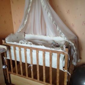 Балдахин из светлой ткани над кроваткой ребенка