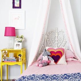 Желтая тумбочка перед кроватью девочки