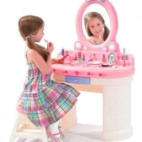 Юная модница перед зеркалом на столике