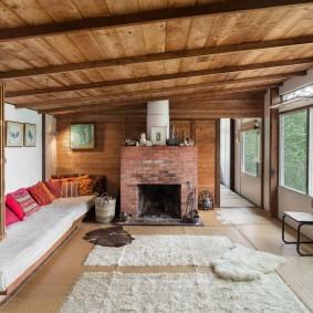 Кирпичный камин в комнате с деревянным потолком