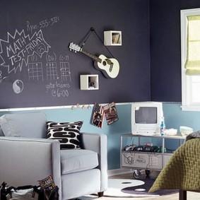 Детская гитара на серой стене