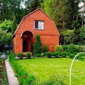 Зеленый газон перед кирпичным домиком