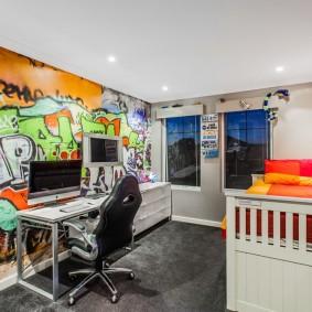 Компьютерный стол перед стеной с граффити