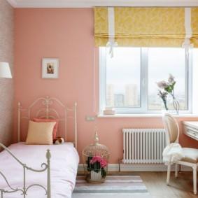 Металлическая кровать в комнате с розовой стеной