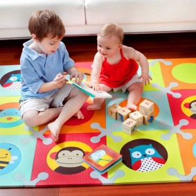 Маленькие детки на мягком игровом коврике