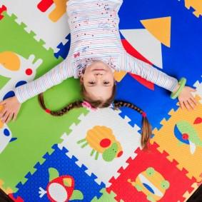 Девочка дошкольного возраста на ярком коврике