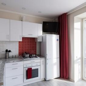 Белый холодильник возле красной шторы