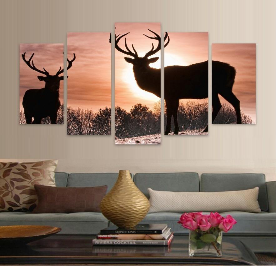 Фото оленя на стене над диваном