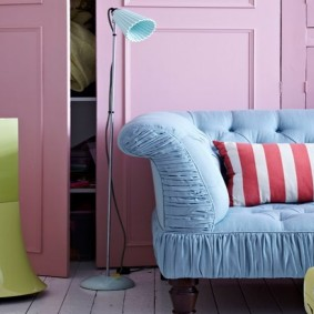 Голубой диван в комнате с розовыми стенами